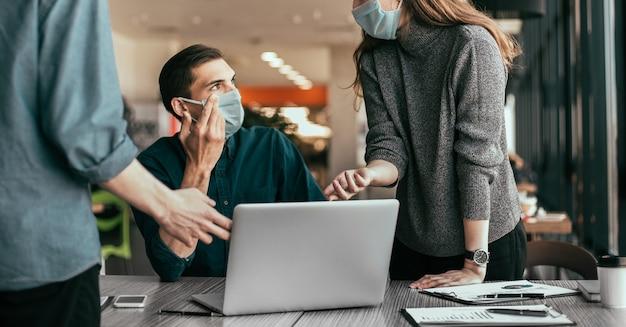 Employés portant des masques de protection discutant des problèmes de travail