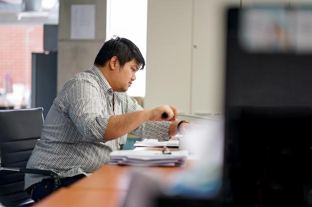 Les employés préparent des documents au bureau. avec machine à relier