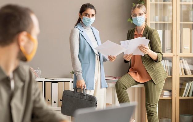 Les employés de retour au travail avec des masques faciaux