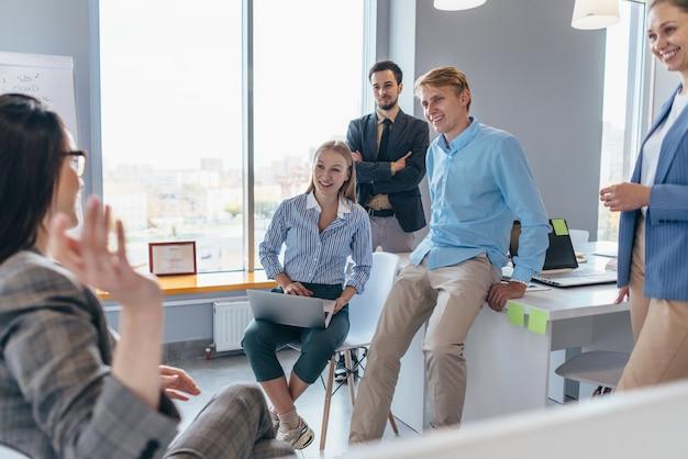 Les employés se rassemblent dans le bureau et écoutent leur collègue parler.