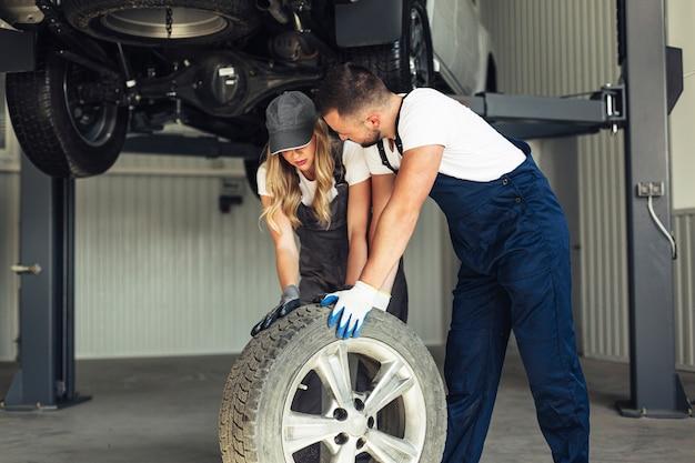 Employés de service automobile poussant la roue