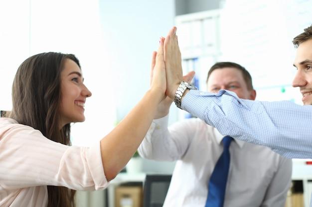 Des employés souriants célèbrent le succès au travail