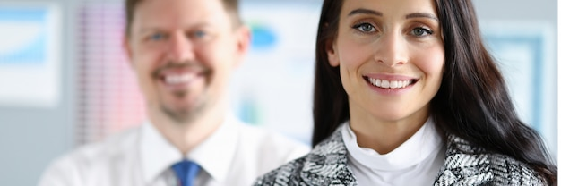 Employés souriants homme et femme se tiennent dans le portrait de bureau