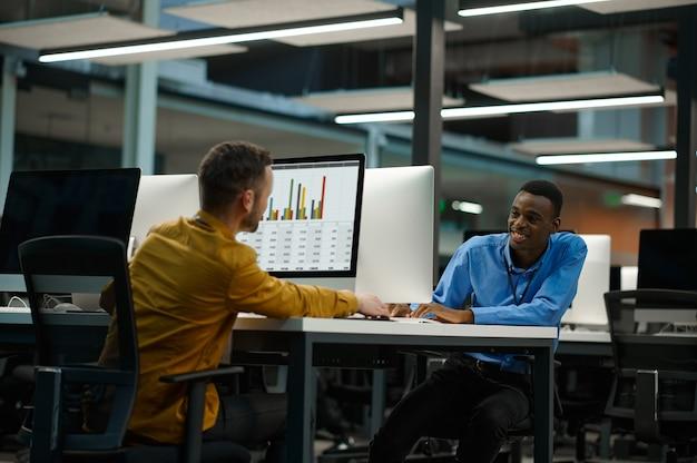 Les employés travaillent sur des ordinateurs, sur le lieu de travail dans un bureau informatique. travail d'équipe et planification professionnels, remue-méninges de groupe, intérieur d'entreprise moderne en arrière-plan