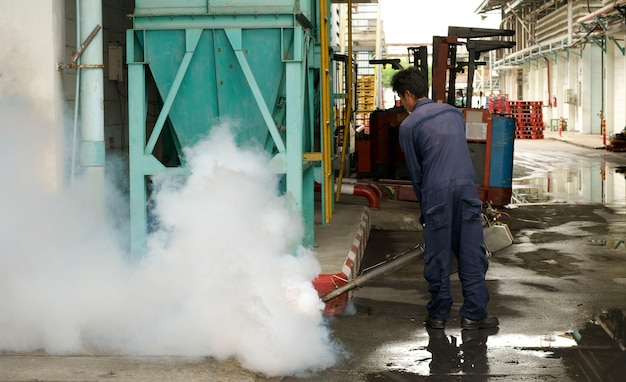 Les employés tuent les moustiques en pulvérisant des produits chimiques dans la factore