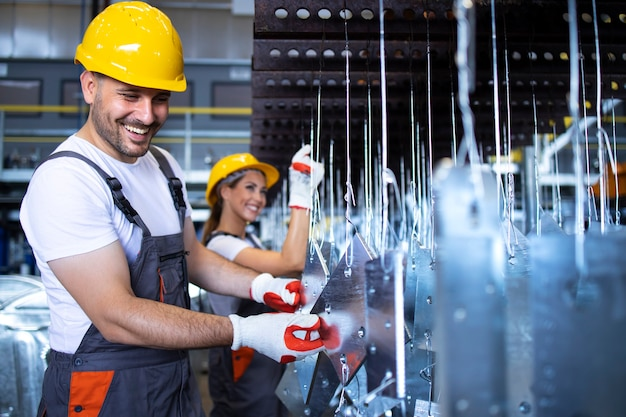 Employés d'usine avec des casques jaunes inspectant les pièces métalliques dans l'usine automobile
