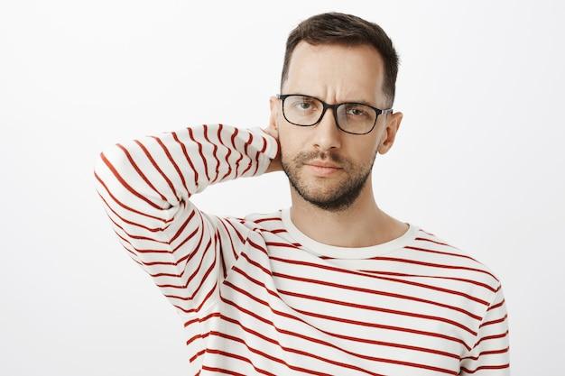 Employeur masculin adulte fatigué et déçu dans des lunettes noires, touchant l'arrière de la tête et fronçant les sourcils, à la concentration