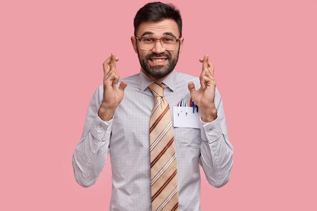 Un employeur positif met tous ses efforts à prier, croise les doigts avec anticipation, veut que les rêves deviennent réalité, habillés de vêtements