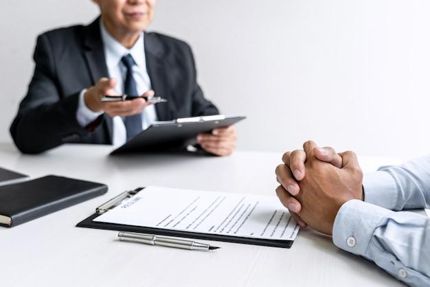 L'employeur s'entretient pour demander au demandeur d'emploi masculin de parler de recrutement.
