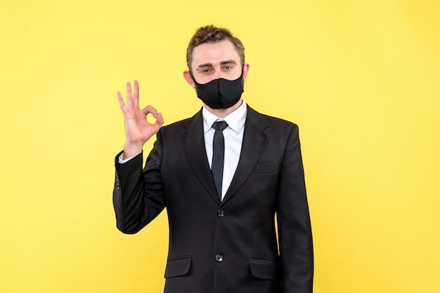 Employeur senior faisant un geste ok en se tenant debout sur jaune