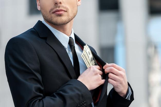 Empocher l'argent de l'entreprise. photo recadrée d'un homme d'affaires mettant de l'argent dans sa poche