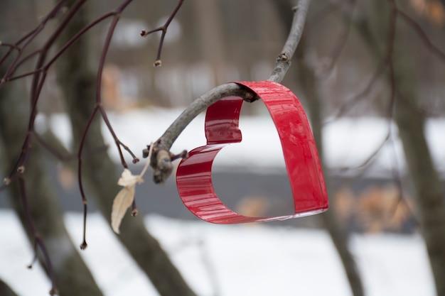 Emporte-pièce en forme de coeur suspendu à un arbre avec une mise au point sélective de fond de neige d'hiver