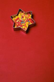 Emporte-pièce en forme d'étoile de noël en pain d'épice rempli de pépites de sucre colorées sur fond rouge. espace de copie. carte de noël