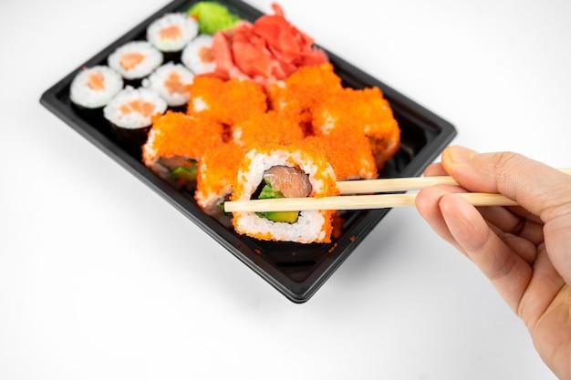 Emporter des rouleaux de sushi dans un contenant en plastique, california, maki roll saumon, gingembre rose, wasabi. concept de livraison de sushi