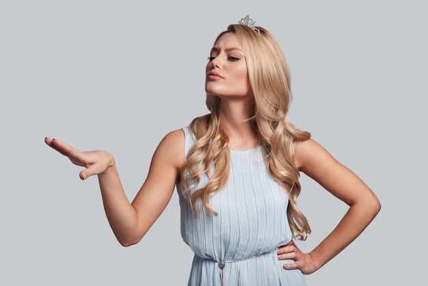 Emportez ça ! jeune femme fière en couronne gardant la main sur la hanche et regardant loin en se tenant debout sur fond gris