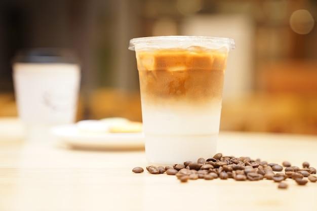Emportez latte avec grain de café sur la table en bois