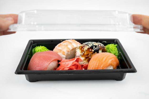 Emportez les sushis dans un contenant en plastique, gingembre rose, wasabi. concept de livraison de sushi