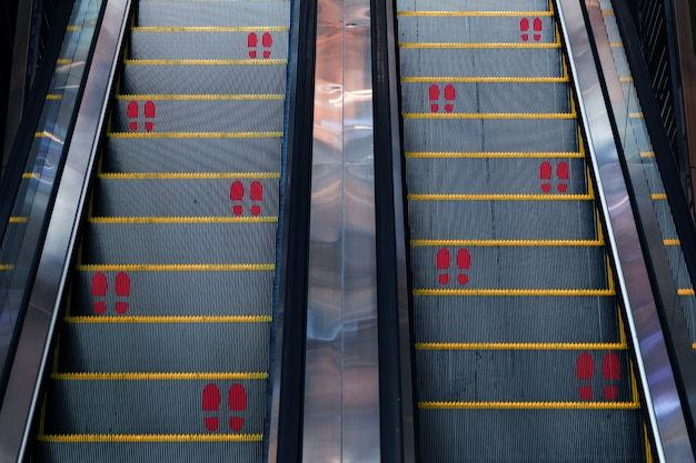 Empreinte d'autocollant pour garder le symbole de distance sociale sur l'escalator de la nouvelle norme