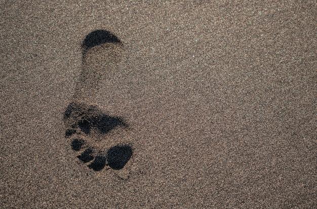 Empreinte dans le sable de la plage volcanique sombre, avec la lumière du soleil, tenerife, îles canaries, espagne
