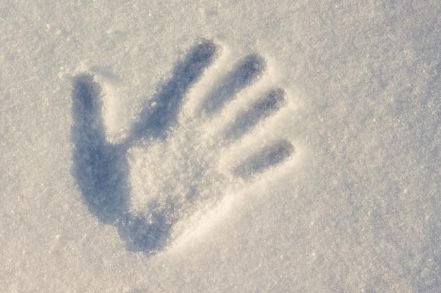 Empreinte de main sur blanc avec une teinte bleue de neige avec une journée ensoleillée d'hiver