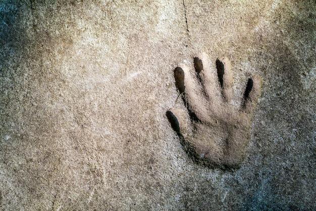 Empreinte de main mémorable d'une main dans un vieux mur de béton