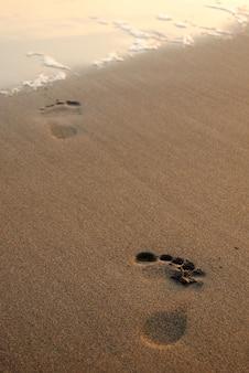 Empreinte de pied dans le sable à la plage