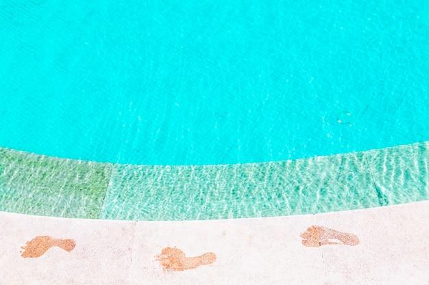 Empreinte pieds nus humides sur le site de la piscine d'eau bleue, vue de dessus