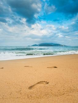Empreinte sur la plage avec l'île derrière. mur de ciel moody