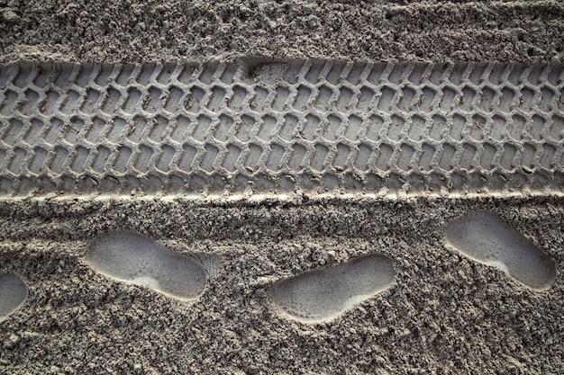 Empreinte de sable de plage humains et pneus