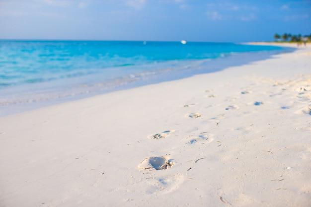 Empreintes humaines sur la plage de sable blanc