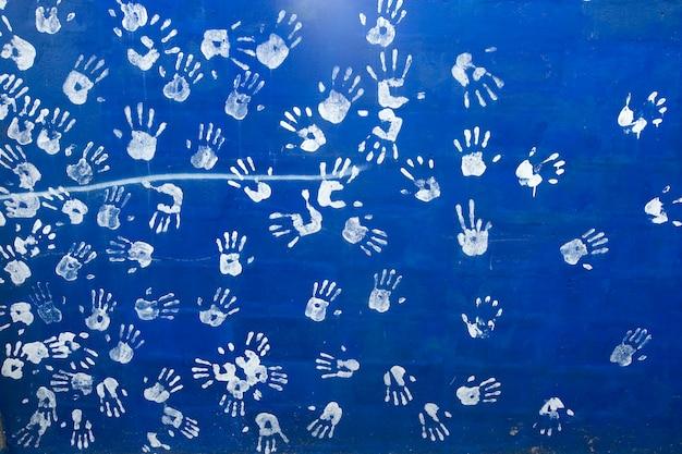Empreintes de mains blanches sur un fond de mur bleu