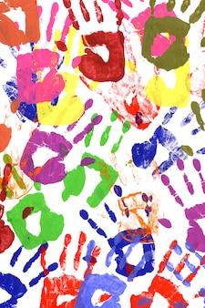 Empreintes de mains peintes à base de peinture acrylique vive sur papier blanc