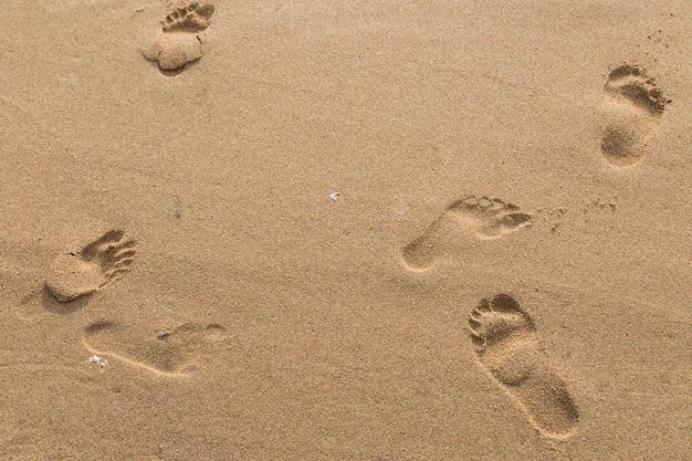 Empreintes de pas d'amoureux dans le sable sur le fond de la plage