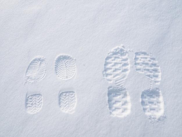 Empreintes de pas de dame et homme sur la neige en hiver.