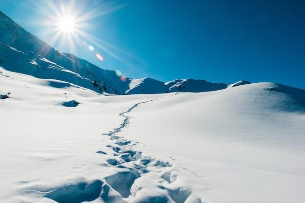 Empreintes de pas dans le paysage des montagnes de neige fraîche beau lever de soleil d'hiver aventure et temps de voyage