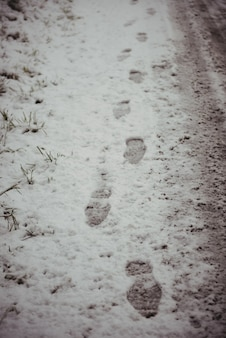 Empreintes de pas dans la route enneigée