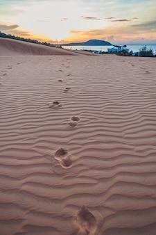 Empreintes de pas dans le sable dans le désert rouge au lever du soleil.