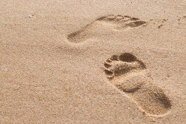 Empreintes de pas dans le sable sur le fond de la plage