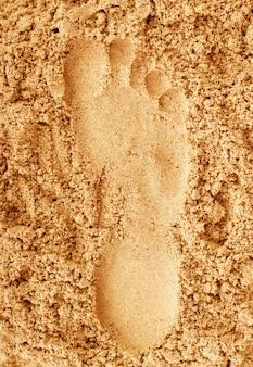 Empreintes de pas dans le sable à la plage