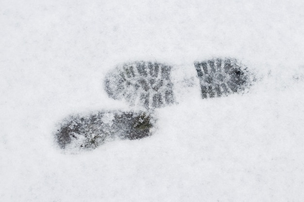 Empreintes de pas d'un homme sur la neige blanche en hiver, fond d'hiver