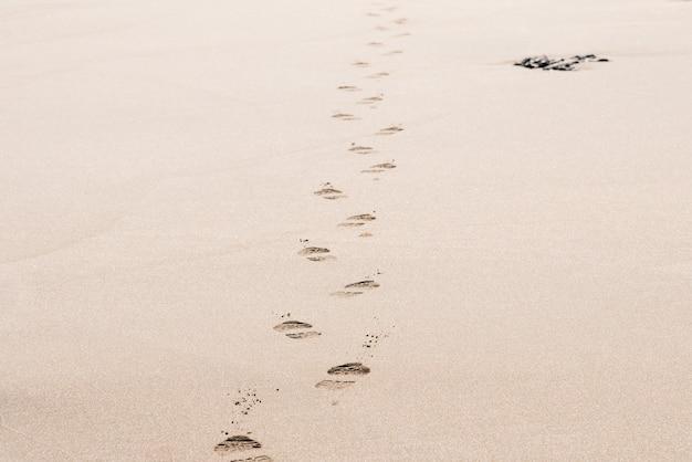 Empreintes de pas d'un homme sur le sable du désert par une journée ensoleillée