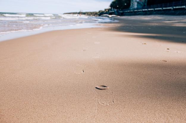 Empreintes de pas d'une personne dans le sable humide d'une plage