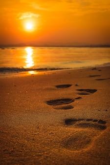 Empreintes de pas sur la plage au coucher du soleil
