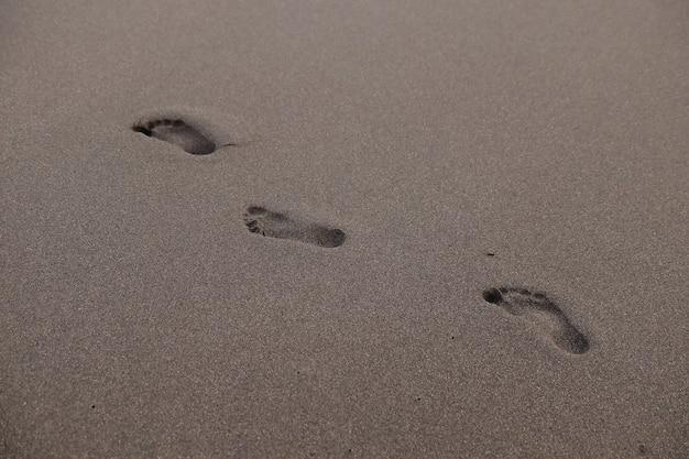 Empreintes de pas sur la plage pendant le coucher du soleil en été