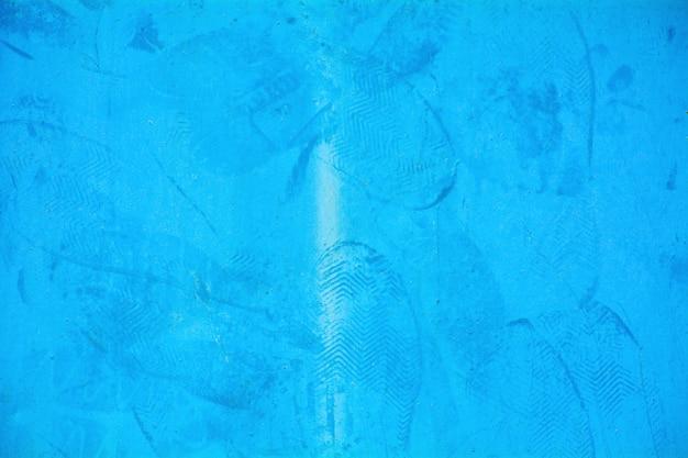 Empreintes de pas sur la plaque de fer bleue