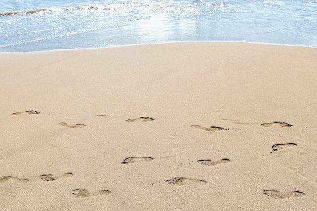 Empreintes de pas sur le sable de la plage
