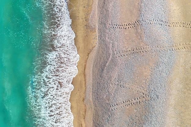 Empreintes de pas de tortue menant de la mer à travers l'une des plages de sable de chypre, vue aérienne directement au-dessus