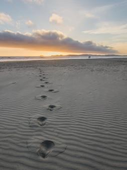 Empreintes de pieds dans le sable gris
