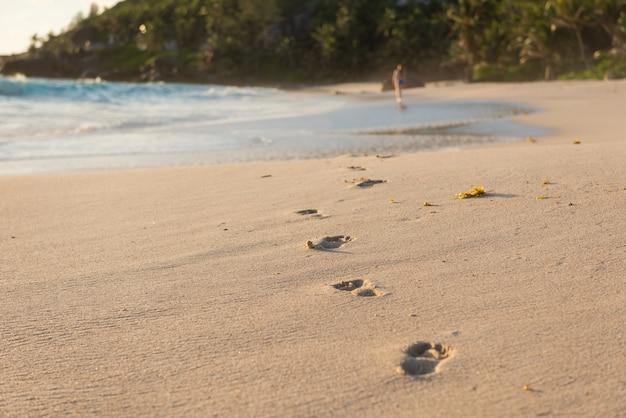 Empreintes de pieds nus humains profonds et femme loin
