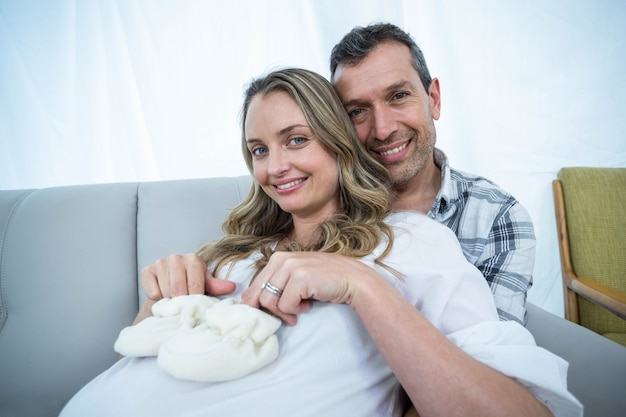 Enceinte couple assis sur le canapé avec des chaussures de bébé sur le ventre dans le salon